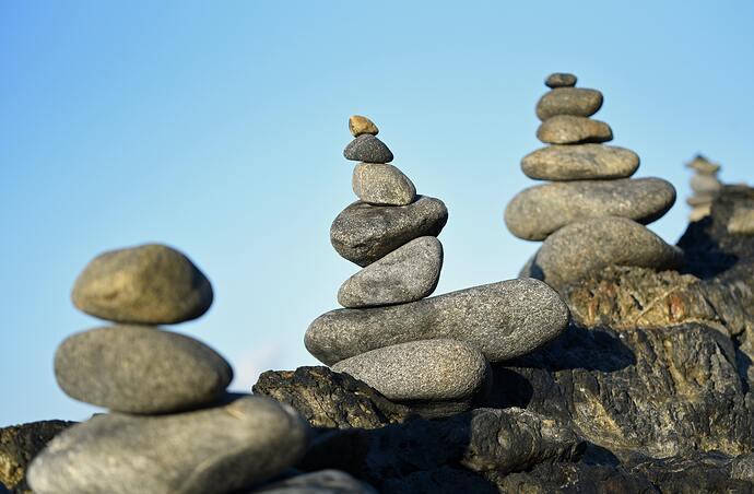 Three piles of balancing rocks against blue sky